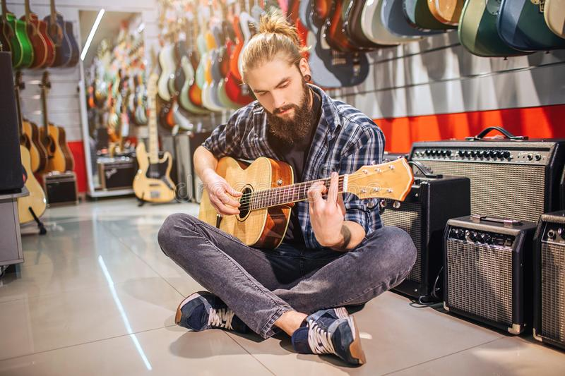 Calm and concentrated young man sit on floor with legs crossed. He playes on acoustic guitar. Many electric guitars and royalty free stock images