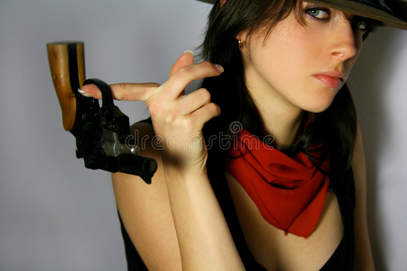 Calm cowgirl. Woman with red kerchief is holding a gun royalty free stock images