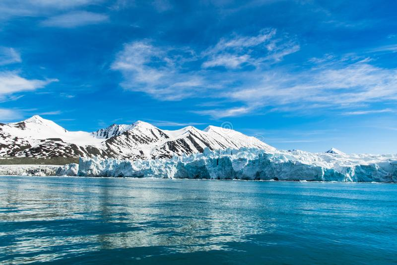 Arctic Landscape in Svalbard - North Pole, when the glaciers meet a sea. Calm and crystal clear water, icebergs, glaciers and amazing mountains covered in snow stock photos