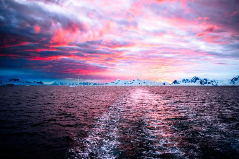 Antarctic Landscape - Antarctica Peninsula at sunset, with a gorgeous colored sjy. Calm and dark water, icebergs, glaciers and amazing mountains covered in snow royalty free stock photography