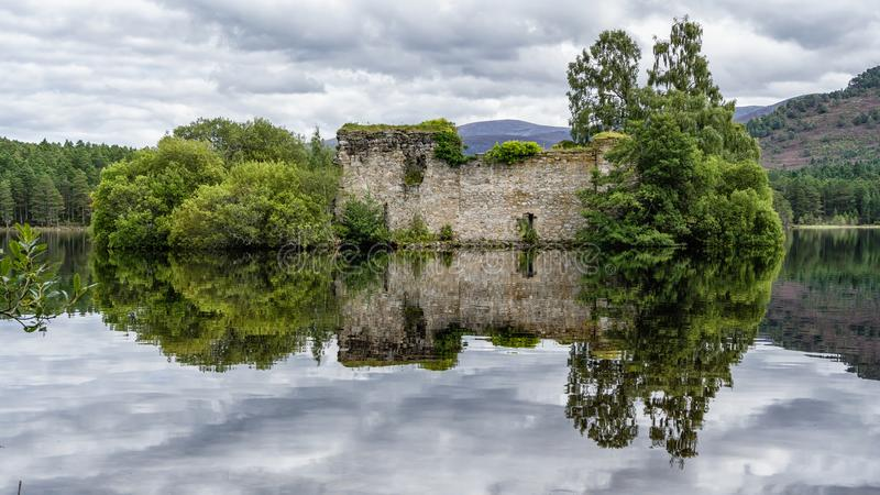 Reflected Castle. On a calm day the castle at Loch an Eilein on Speyside in the Scottish Highlands appears to float on the waters of the loch royalty free stock images