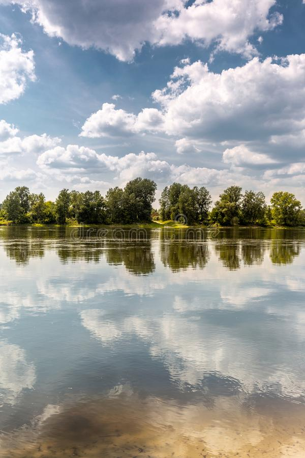 Calm day at river bank. Lazy summer day at river bank. Line of trees at oposite bank makes symmetry royalty free stock photography