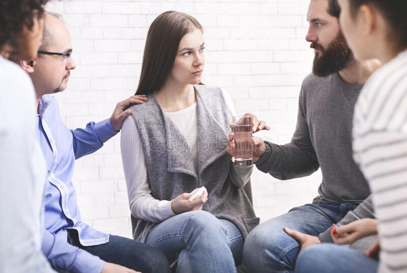 Therapy group members comforting upset woman at community meeting in rehab royalty free stock image