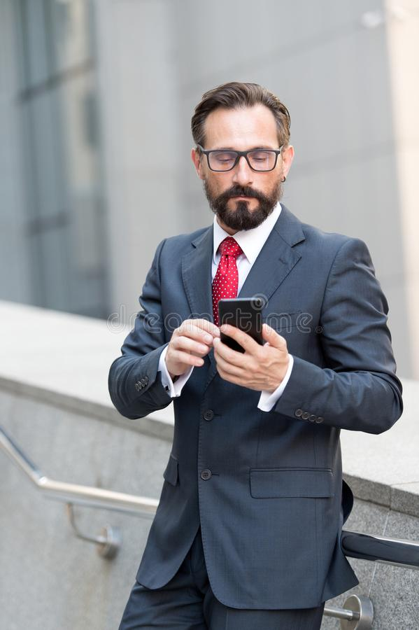 Calm elegant man looking at the screen of his smartphone while being alone royalty free stock image