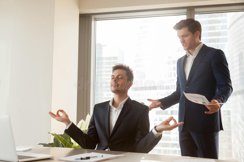 Calm employee meditating at workplace, angry boss shouting, stre stock images