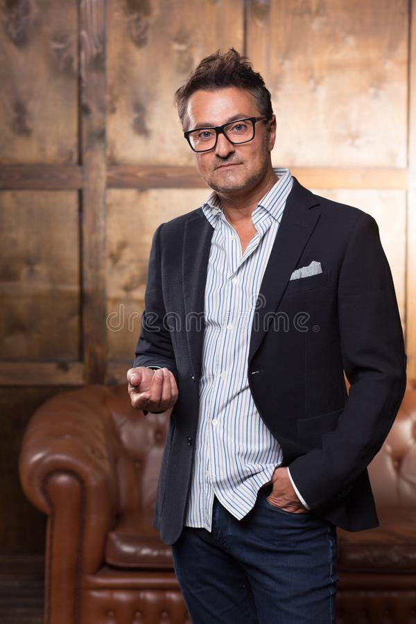 Calm European man looking at you and putting one hand forward royalty free stock photography
