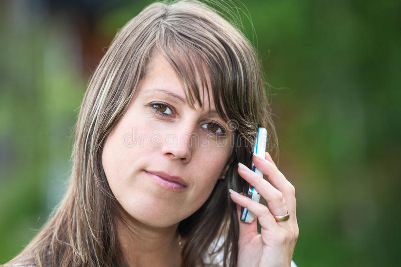 Calm face close-up with mobile phone. Caucasian woman calm face close-up with mobile phone stock photography