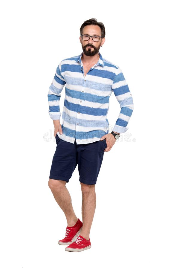 Calm fashionable bearded man expressing calmness and keeping his hands in pockets royalty free stock images
