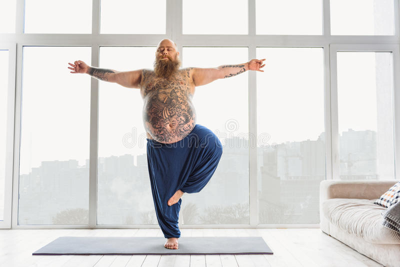 Calm fat man relaxing with meditation stock images