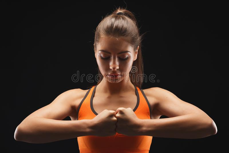Calm female fighter ready to fight over black background royalty free stock photo