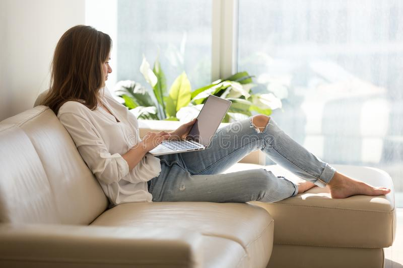 Happy female browsing internet sitting on sofa at home stock images