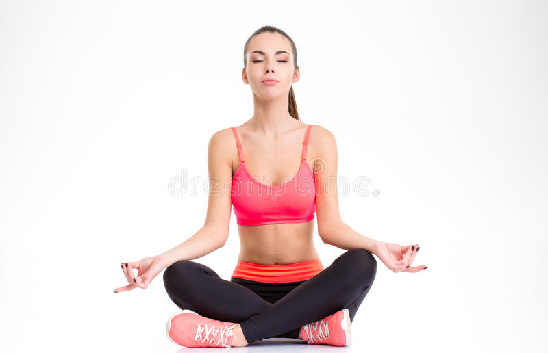 Calm fitness girl sitting in lotus position with eyes closed. Concentrated calm fitness girl sitting in lotus position with eyes closed isolated over white stock photos
