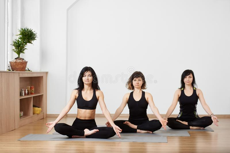 Calm fitness women resting while sitting and meditating in lotus asana. Yoga classes in gym. Easy yoga asana. Copy space stock images