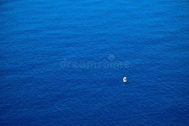 Calm flat surface of ocean and small fisher boat. Mediterranean Sea. royalty free stock photos
