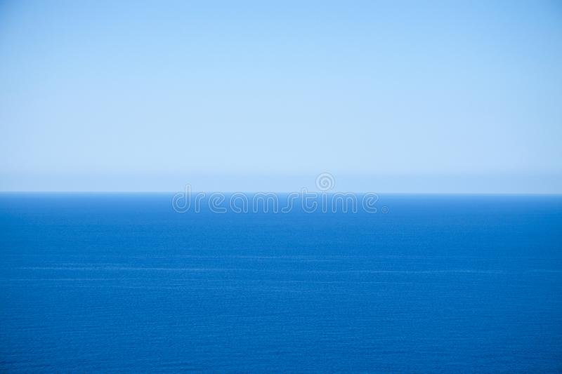 Calm flat surface of sea and cloudless clear blue sky at horison. Near Balos lagoon. Crete, Greece stock photo