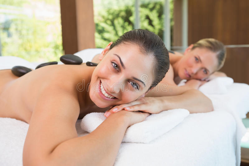 Calm friends lying on massage tables with hot stones on their backs royalty free stock image