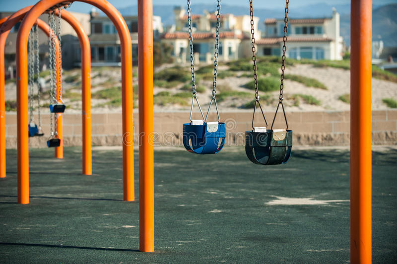Calm before the fun begins. Empty playground swings swaying in the ocean breeze at the neighborhood beach in the morning stock image