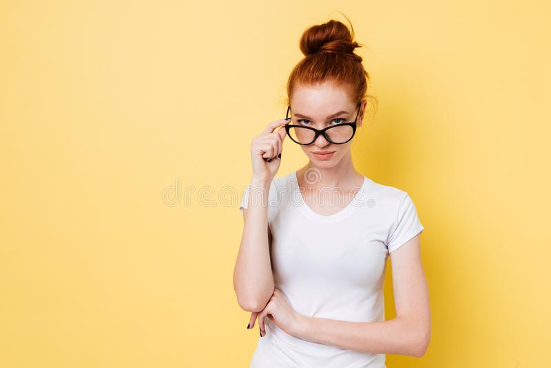 Calm ginger woman in eyeglasses looking through eyeglasses at camera royalty free stock images