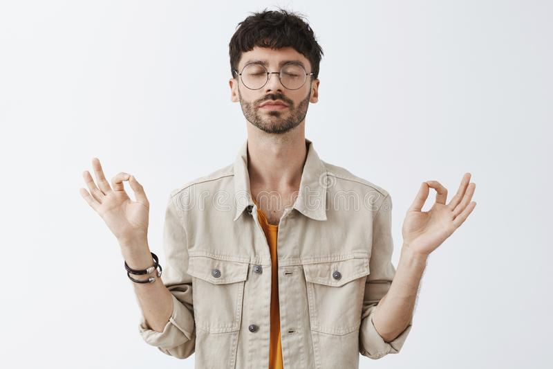 Calm good-looking and stylish urban guy with beard and trendy hairstyle in glasses meditating to relieve from stress royalty free stock image