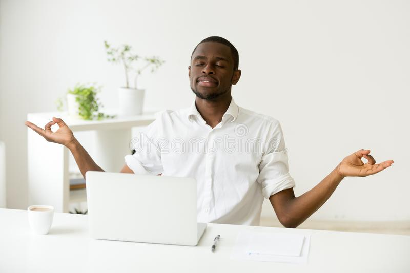 Calm happy african man meditating at office desk with laptop. Calm happy african american man meditating at home office desk with laptop developing focus and royalty free stock photos