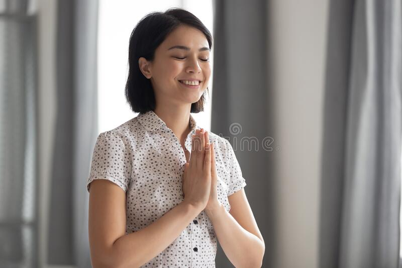 Happy woman worker feel thankful meditating at workplace stock photos
