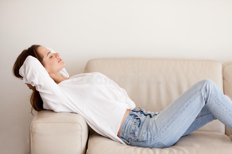 Calm happy millennial woman relaxing on comfortable couch at hom royalty free stock photo