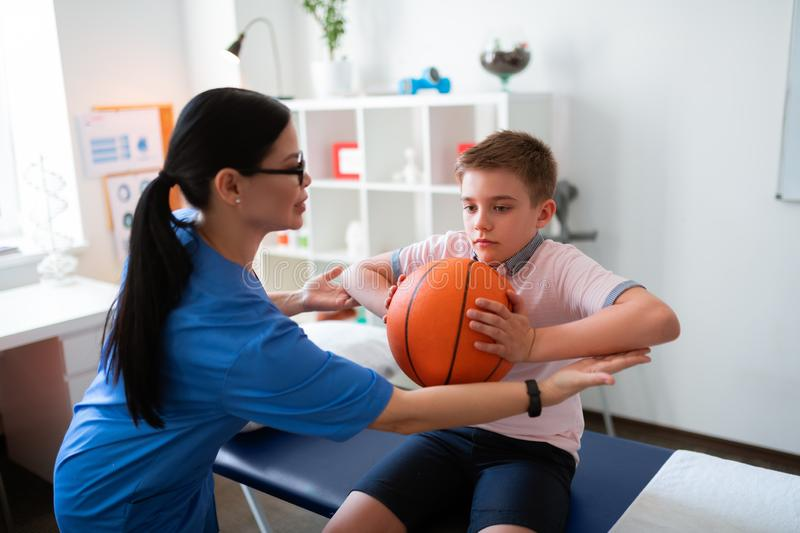 Calm hard-working boy sitting on the daybed and pushing hands into basketball ball royalty free stock images