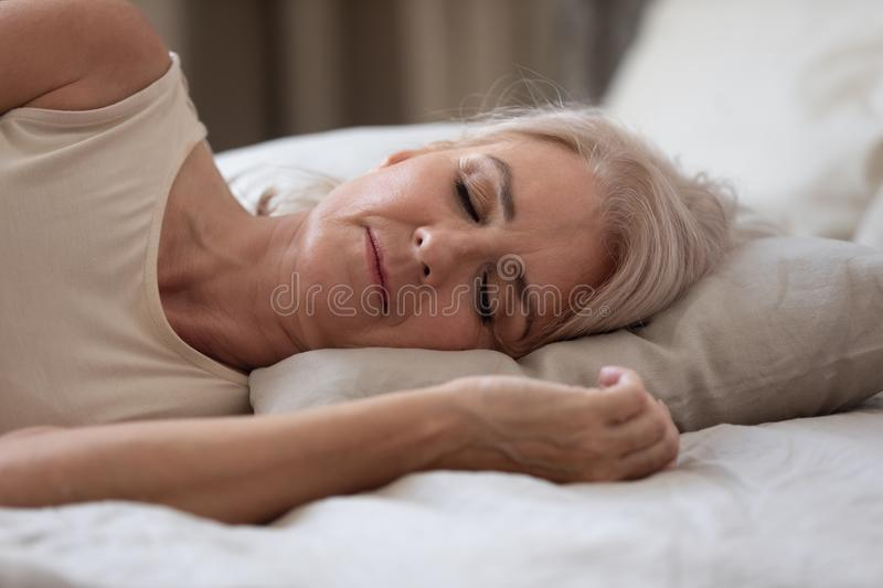 Calm serene older woman sleeping alone in bed, closeup view stock photography