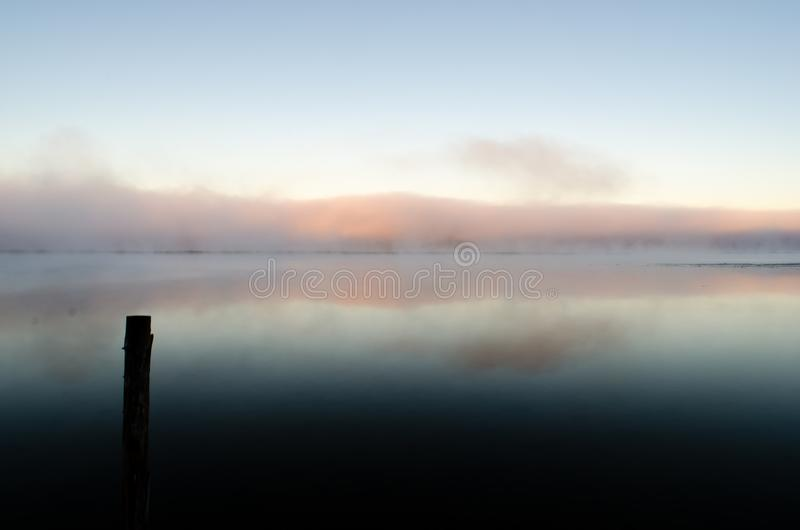 A calm inlet at dawn viewed from a dock as mist rises from the water and tinged orange by the rising sun stock images