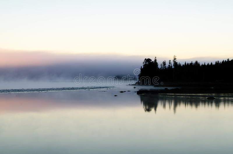 A forested  jetty pokes into the calm inlet and the extended reef at low tide can be seen. The forested jetty is silhouetted by sun still below the horizon.  It stock image