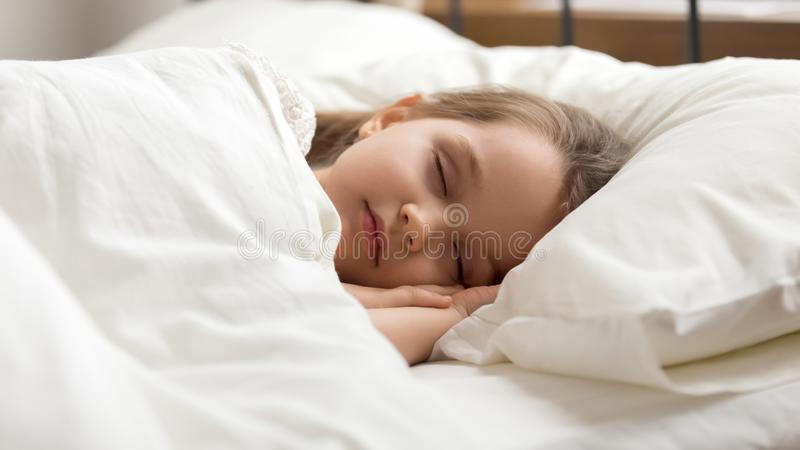 Calm kid girl sleeping in bed covered with warm duvet. Calm kid girl sleeping well alone on soft pillow covered with warm blanket duvet lying in comfortable bed stock photos