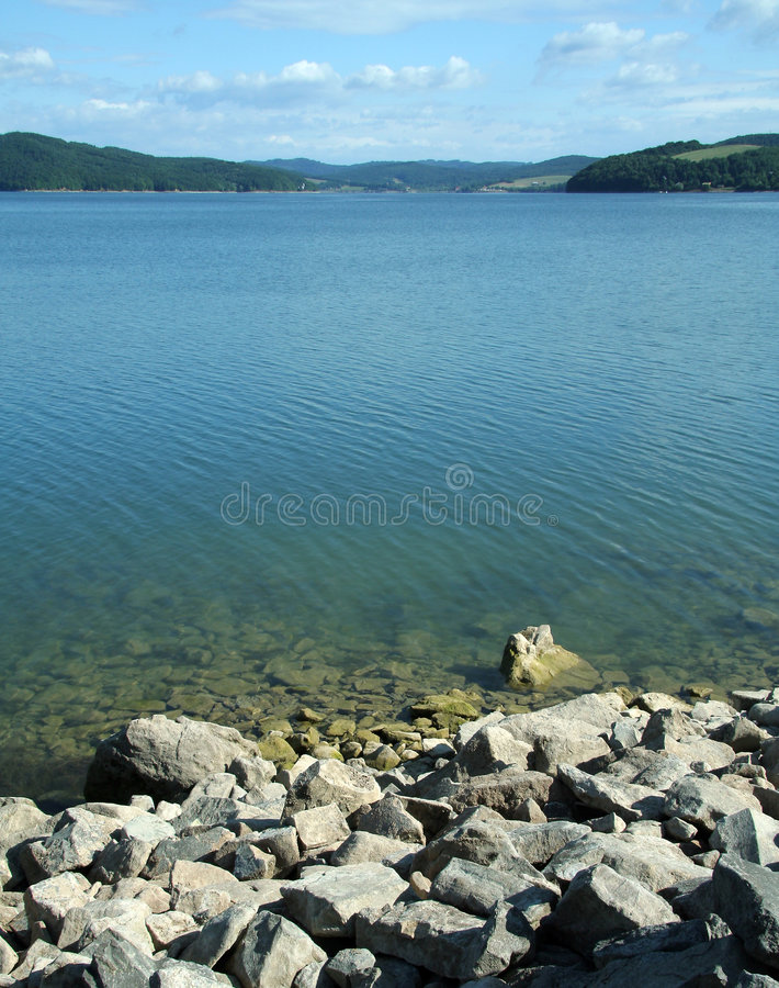 Calm lake. Calm water in small lake; rocks on strand; Domasa lake in eastern Slovakia; summer resort attracted by many local people and polish visitors royalty free stock photo