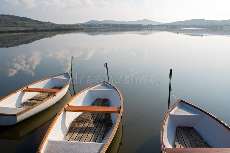 Calm lake. Three boats on a calm lake water surface mirroring the cloudy sky royalty free stock photography