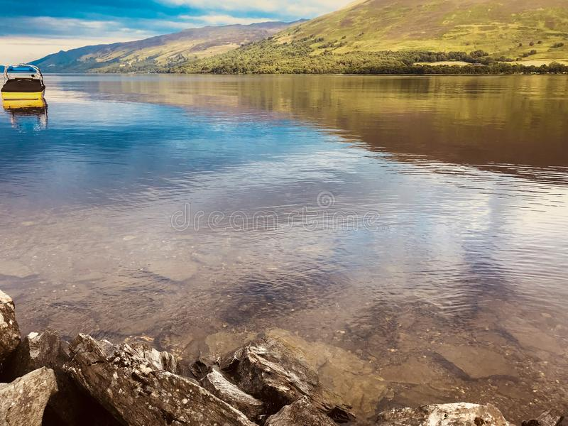 Calm lake with hill background in Scotland. Calm lake with hill background reflecting off the lake in Scotland stock photo