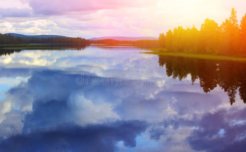 Calm lake. Reflection against the blue sky with white clouds stock photo