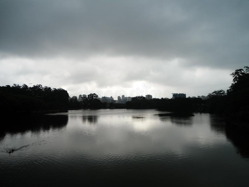 Calm lake with still waters with reflections of a bright but cloudy sky royalty free stock photo