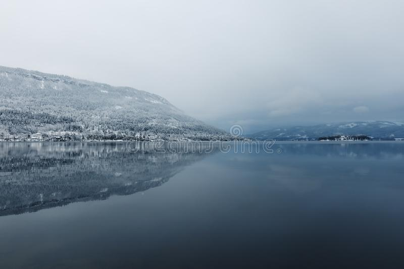 Calm lake in winter. View to calm beautiful lake and mountains in foggy winter day stock images