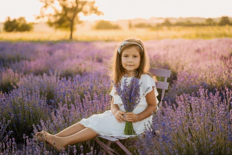 Calm Little Girl auf Lavender Field mit Bouquet stockfoto