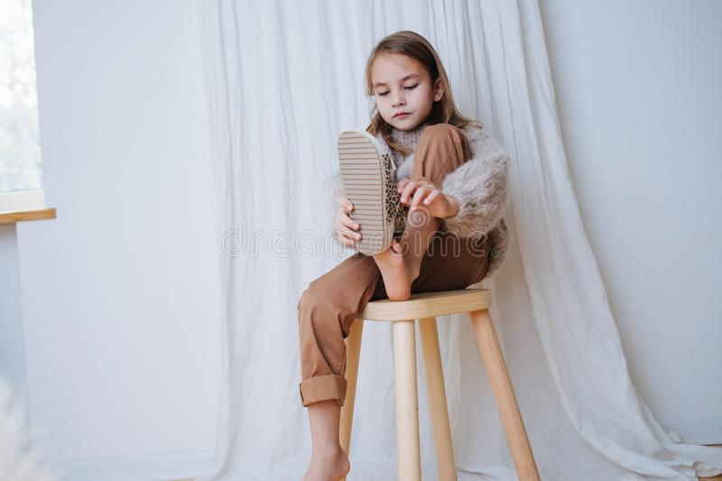 Calm little girl sitting on a stool at home, she`s puting on sandals stock image