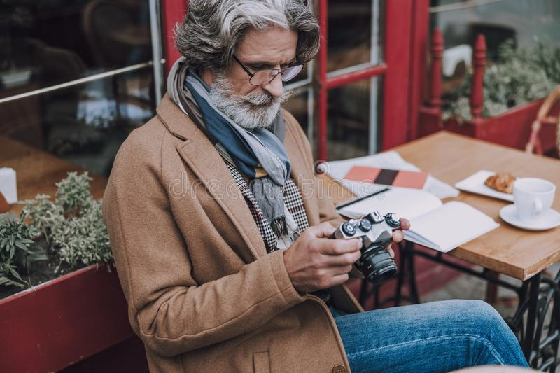 Calm man with camera at the table stock photo royalty free stock image