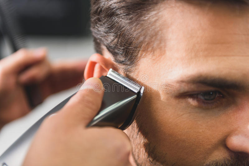 Calm man getting haircut by machine. Close up of hairdresser hand cutting male hair by shearer. Confident man is looking forward with serenity stock photo