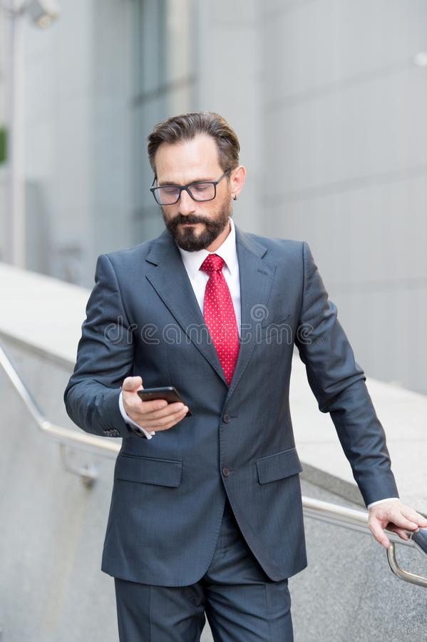 Calm man looking at the smartphone while reading messages. Serious elegant teacher standing outdoors alone and frowning while reading new messages in his royalty free stock image