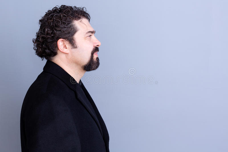 Calm man profile over gray background. Profile of calm handsome dark haired and bearded middle aged man wearing black shirt and blazer over gray background with stock photo