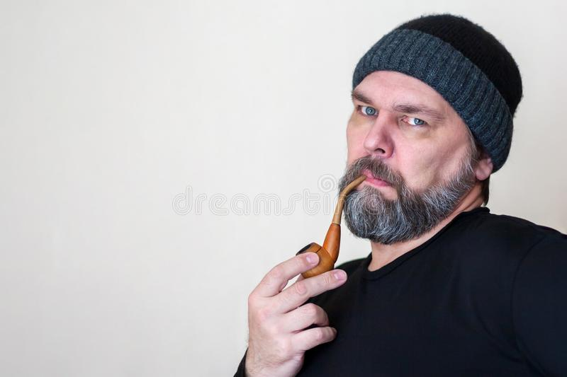 Serious Mature middle-aged man with a beard, Smoking a pipe, looking at the camera. Calm Mature middle-aged man with a beard, Smoking a pipe, looking at the royalty free stock photography