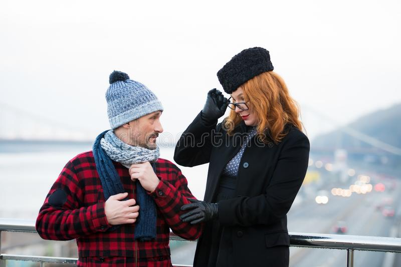 Surprised man looking at stylish lady while being outdoors. Calm middle aged men standing outdoors and turning his head while looking at the women in unusual stock photo