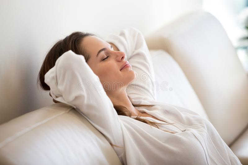 Calm millennial woman relaxing on comfortable sofa breathing fre stock photo