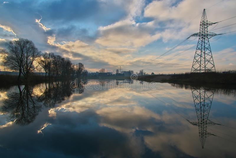 The calm morning landscape with fog and sky over the pond surrounded by trees and electricity towers with the beautiful reflection stock images