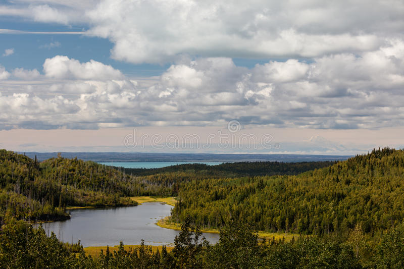 Calm mountain lake high in mountain forests of Alaska Range with snow capped mountains in background royalty free stock photos