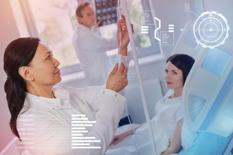 Calm nurse preparing the infusion and her colleague looking at the X ray results royalty free stock photo