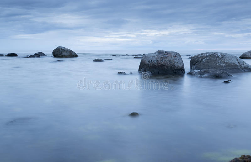 Calm Ocean with Rocks. And blue ocean and sky stock photography